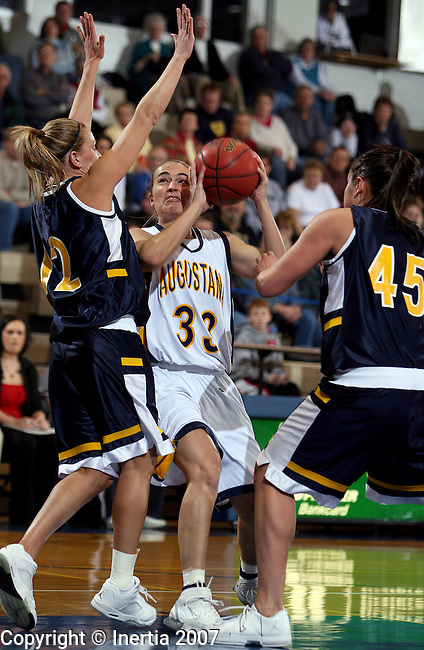SIOUX FALLS, SD - DECEMBER 19:  Megan Doyle, #32, of Augustana College looks for a teammate while being pressured by Tevan Wenbourne, #12, left, and Cassie Iverson, #45 of Mount Marty in the first half Wednesday night at the Elmen Center. (Photo by Dave Eggen/Inertia)