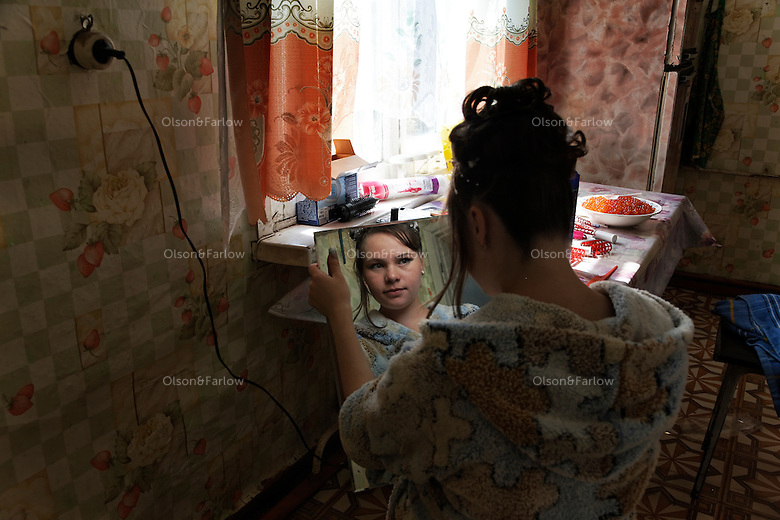 Looking into a mirror, the bride, Miroslava Osipova gets ready on her wedding day.