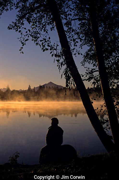 Man silhouetted at sunrise along shoreline sitting on a rock  Washington State USA