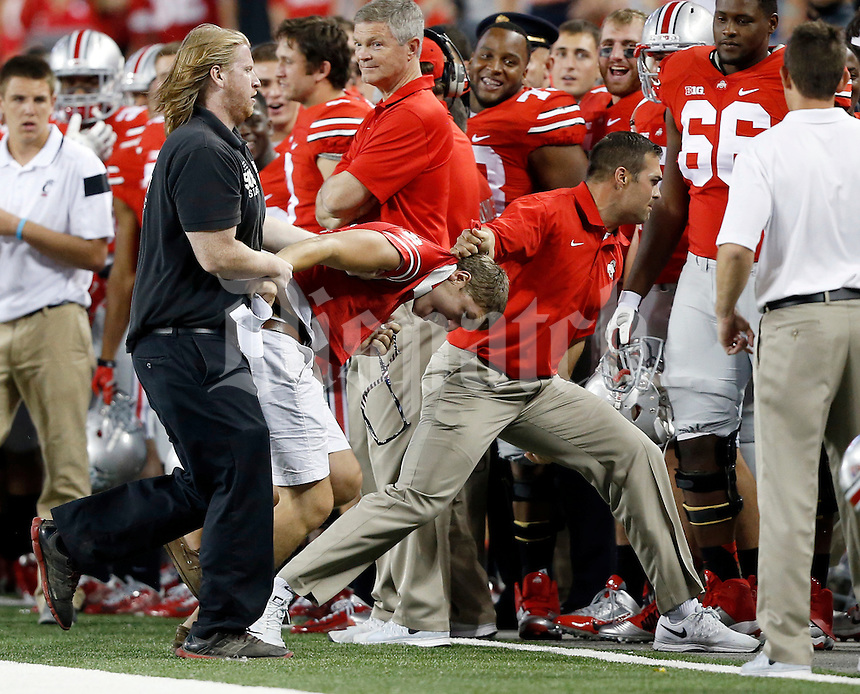 Ohio State strength and conditioning coach Anthony Schlegel tackles a person who ran onto the field during the second quarter of the NCAA football game against the Cincinnati Bearcats at Ohio Stadium in Columbus on Sept. 27, 2014. (Adam Cairns / The Columbus Dispatch)