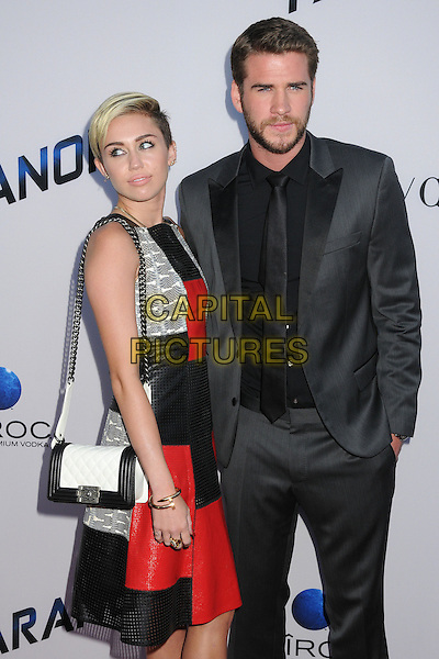 Miley Cyrus, Liam Hemsworth<br /> &quot;Paranoia&quot; Los Angeles Premiere held at the Directors Guild of America, West Hollywood, California, USA, 8th August 2013.<br /> half length red black leather dress sleeveless perforated silver bag white chain strap couple fiance fiancee engaged grey gray suit black shirt tie arm around grey gray snakeskin <br /> CAP/ADM/BP<br /> &copy;Byron Purvis/AdMedia/Capital Pictures