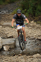 NWA Democrat-Gazette/ANDY SHUPE<br /> Stu Power of Fayetteville rides across Lee Creek Saturday, Sept. 19, 2015, during the Northwest Arkansas Mountain Bike Championships at Devil's Den State park.
