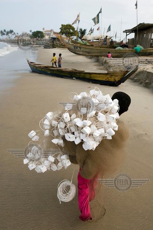 A young boy walks along the beach carrying fishing nets.