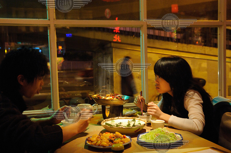Young couple eating at a city restaurant specialising in Northern food.