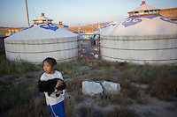 Granddaughter Dula of herder Renqima hugs pet dog Oscar as she strolls outside Mongolian Yurts at her grandmother's dairy farm in Damao Banner, Inner Mongolia, China, October 2014.