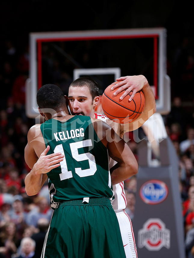 Ohio State Buckeyes guard Aaron Craft (4) embraces Ohio Bobcats guard Nick Kellogg (15) as the buzzer sounds in the second half of the college basketball game between the Ohio State Buckeyes and the Ohio Bobcats at Value City Arena in Columbus, Tuesday evening, November 12, 2013. The Ohio State Buckeyes defeated the Ohio Bobcats 79 - 69. This was the first meeting of the teams in 19 years and the first ever game between them at Value City Arena. (The Columbus Dispatch / Eamon Queeney)