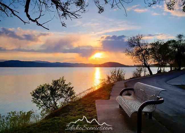 Idaho, North, Kootenai County, Coeur d'Alene. An inviting bench along Coeur d'Alene Lake Drive and the centennial trail at sunset in spring.