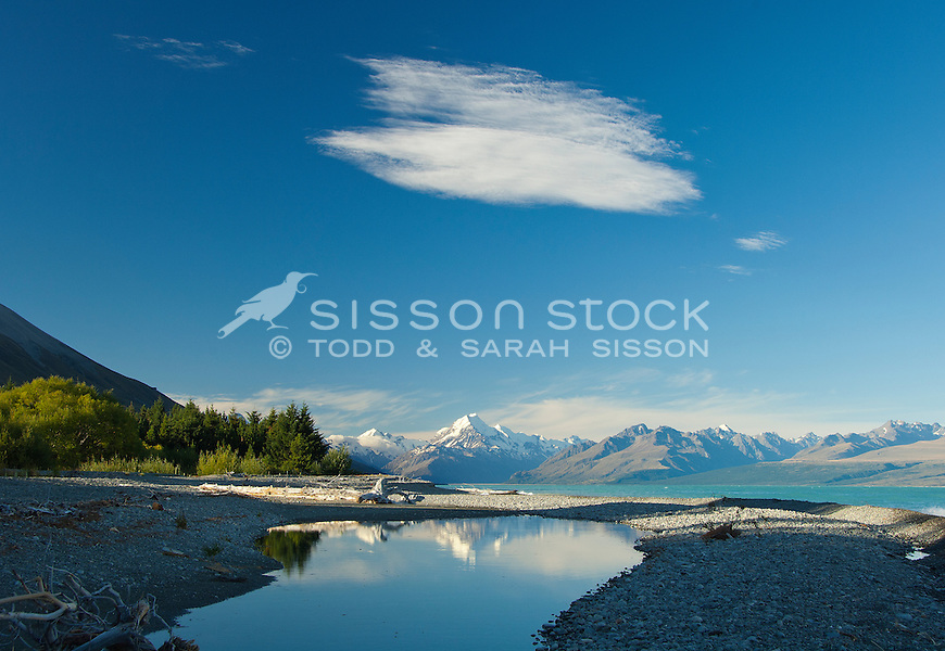 Mount Cook / Aoraki is reflected in a pool calm pool at the edge of Lake Pukaki on a summers day, McKenzie Country