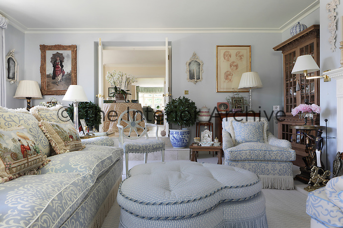 In the living room, a pair of Oriental style needlework cushions adorn the blue and white sofa