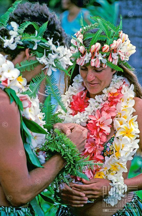 Couple getting married in Hawaii with flowers leis and ti leaf skirts.