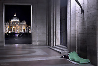 homeless people sleeping near St. Peter's Square, with St. Peter's Basilica with Christmas tree in the background.on Vatican 8 december 2017