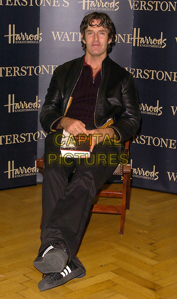 RUPERT EVERETT.At his Booksinging at Waterstones, Harrods, .London, England, October 7th 2006..full length black leather jacket book signing sitting.Ref: CAN.www.capitalpictures.com.sales@capitalpictures.com.©Can Nguyen/Capital Pictures