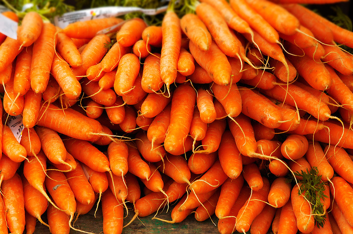 Bunches of Organic carrots with their leaves on a market stall France