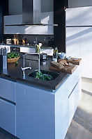 A stainless steel extractor hangs over a central kitchen island