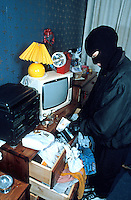 Burglar wearing a balaclava and gloves so as he cannot be identified or traced through his fingerprints has broken into a house and is ransacking through all the drawers for items to steal. This image may only be used to portray the subject in a positive manner..©shoutpictures.com..john@shoutpictures.com.