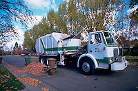 Robotic arms on a high-tech trash truck pick up a trash barrel, allowing for automated trash collection.
