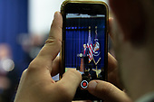 An event attendee takes a cell phone photo as United States President Donald Trump delivers remarks to a group of young adults at the White House in Washington, DC on June 27, 2018. Credit: Alex Edelman / CNP