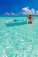 A woman wades in the crystal clear waters of Alabaster Bay, holding on to two rustic Bahamian style dorys, one adorned with Queen Conch Shells, Eleuthera, Bahamas, Atlantic Ocean (MR)