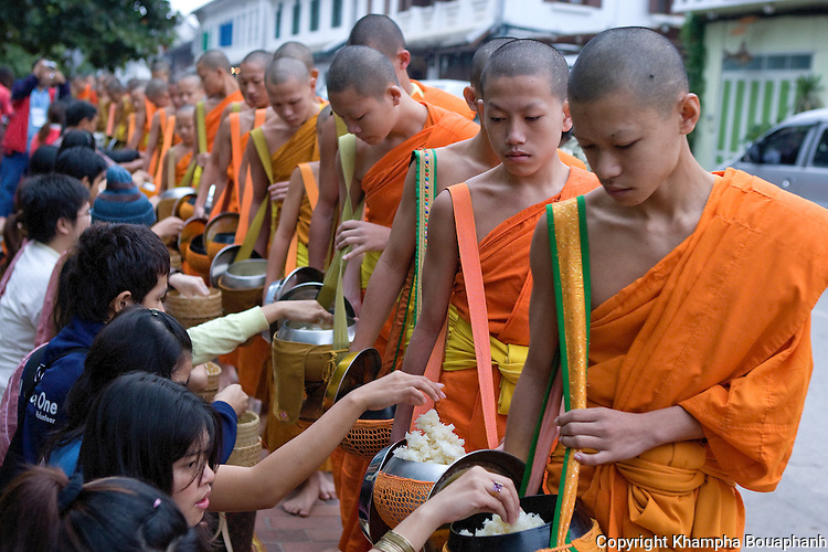 Buddhist monks make their morning alms round in Luang Prabang, Laos on November 6, 2009.   (Photo by Khampha Bouaphanh)