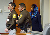 Mildred Muhammad, ex wife, of convicted sniper John Allen Muhammad, is protected by two Virginia Beach Sheriff's deputies as the defense, including Muhammad, and prosecution approach the bench during her testimony in the penalty phase of the trial in Virginia Beach Circuit Court in Virginia Beach, Virginia on November 19, 2003.   Mildred is moved to the corner of the court and protected by the deputies while Muhammad is up at the bench. Now in the punishment phase of the trial, the jury can only choose execution or life in prison without parole for Muhammad, who was found guilty Monday, November 17, 2003 of all charges, including two capital murder counts, in one of 10 fatal shootings that terrorized the Washington, D.C., area in 2002. <br /> Credit: Tracy Woodward - Pool via CNP