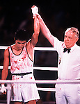 A bloodied Japanese boxer stands victorious at the 1984 Los Angeles Olympic Games.