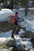 A adult male hiker crosses a river on a hiking trail in the  White Mountains, New Hampshire USA during the spring months
