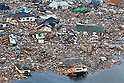 Houses washed away by a tsunami in Natori, Miyagi Prefecture at 7.31am March 12th, 2011. Below the roof to the lower right a victim can be seen. A huge M8.9 earthquake hit Japan on Friday 11th March, 2011 followed by a giant tsunami causing death and destruction