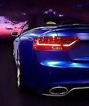 Closeup of a taillight on the back of a blue car on a highway at sunset. 2015 Audi RS 5 cabriolet.