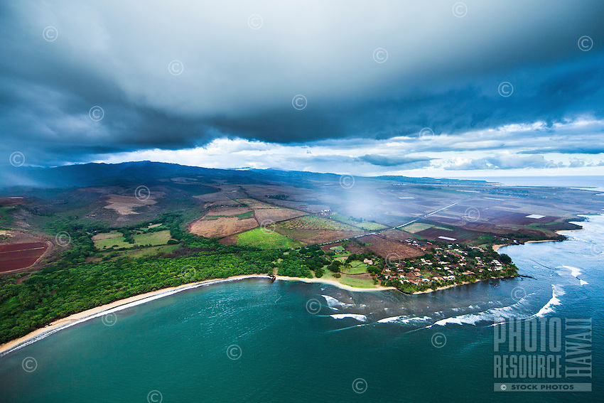 An aerial shot of rainclouds rolling over the west end of Kaua'i, with a long stretch of beach visible to the left.