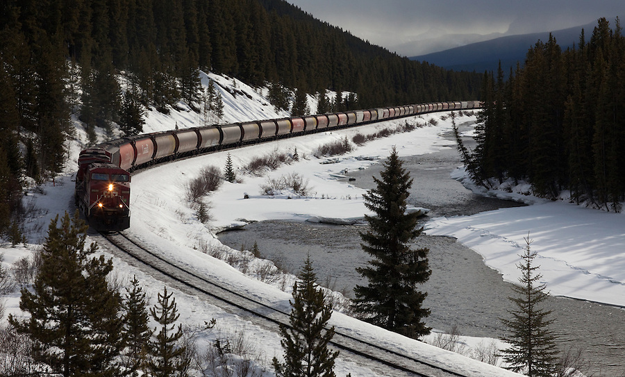 A train powers through Morant's Curve in Banff National Park, Alberta, Canada during the winter.