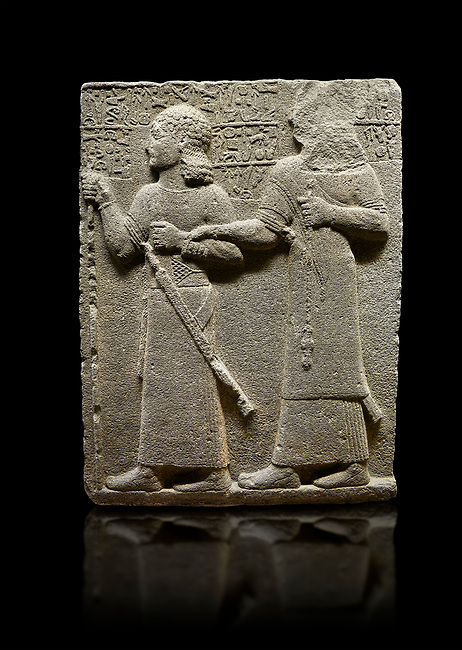 """Hittite monumental relief sculpted orthostat stone panel of Royal Buttress. Basalt, Karkamıs, (Kargamıs), Carchemish (Karkemish), 900-700 B.C. Anatolian Civilisations Museum, Ankara, Turkey.<br /> <br /> King Araras holds his son Kamanis from the wrist. King carries a sceptre in his hand and a sword at his waist while the prince leans on a stick and carries a sword on his shoulder. <br /> <br /> Hieroglyphs reads; """"This is Kamanis and his siblings. I held his hand and despite the fact that he is a child, I located him on the temple. This is Yariris' image"""".  <br /> <br /> Against a black background."""