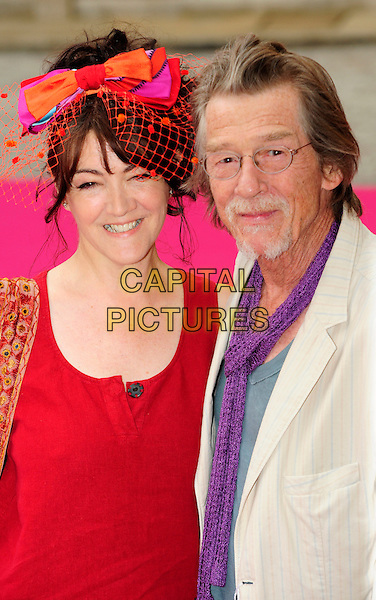 ANWEN REES MYERS &amp; JOHN HURT <br /> Royal Academy Summer Exhibition 2010, Royal Academy Of Arts, London, <br /> England, UK, June 9th 2010.<br /> half length red bow netting net hat top tunic dress pink couple wife husband glasses beige cream jacket goatee facial hair purple scarf <br /> CAP/CJ<br /> &copy;Chris Joseph/Capital Pictures