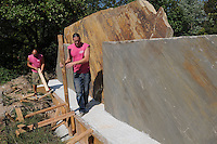 NWA Democrat-Gazette/FLIP PUTTHOFF <br /> NEW LOOK FOR SIGNS<br /> Terrance McCoy (left) and Willie Parker remove forms from concrete while working Tuesday Sept. 15 2015 on a project to remodel two stone signs that welcome travelers to Bella Vista. Large stone signs at the south and north edges of the city along U.S. 71 are being redone, Parker said. The two are shown here working on the north sign.