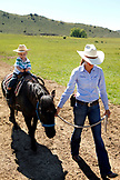 USA, Wyoming, Encampment, a wrangler leads a young boy on a pony, AbarA Ranch