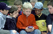 Boys play with a Gameboy.