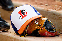 A Durham Bulls cap sits on top of a glove in the dugout during the International League game against the Gwinnett Braves at Durham Bulls Athletic Park on July 27, 2011 in Durham, North Carolina.  The Bulls defeated the Braves 4-0.   (Brian Westerholt / Four Seam Images)