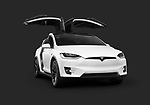 White 2018 Tesla Model X luxury SUV electric car with open falcon wing doors isolated on dark gray black background with clipping path