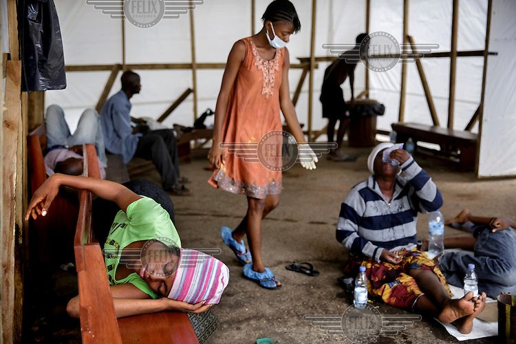 Isha Kamara (orange dress), who is symptom free, assists eight members of her family, the Fofana-Kamaras, who have become ill with ebola-like symptoms and are lying inside a tent outside the Connaught Hospital hoping that they will soon be tested and receive treatment. Since there is no bed capacity at the moment, patients (who potentially pose a great risk) are forced to stay hours and days in a tent outside the hospital without any treatment. The floor of the tent is covered with body liquids which are potentially highly contaminated with ebola virus.