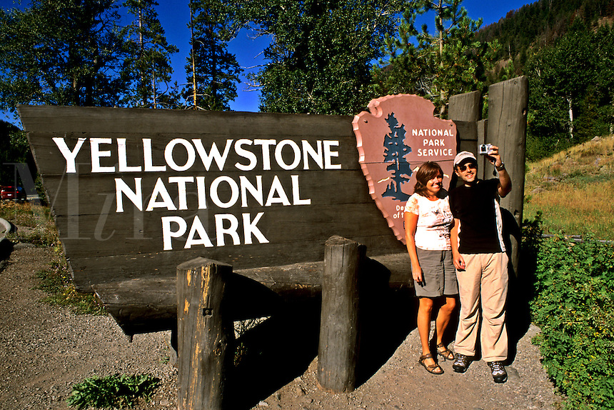 Tourist couple having fun with camera at Yellowstone National Park in Wyoming