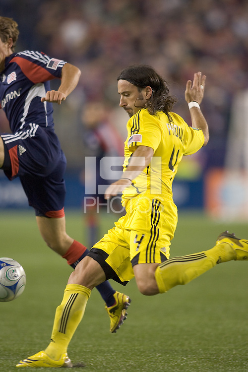 Columbus Crew defender Gino Padula (4) winds up to clear the ball as New England Revolution midfielder Wells Thompson (7) defends. The Columbus Crew defeated the New England Revolution, 1-0, at Gillette Stadium on October 10, 2009.