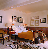 A colonial style bedroom with a tier of antique suitcases at the foot of the bed and framed prints of animals on the walls