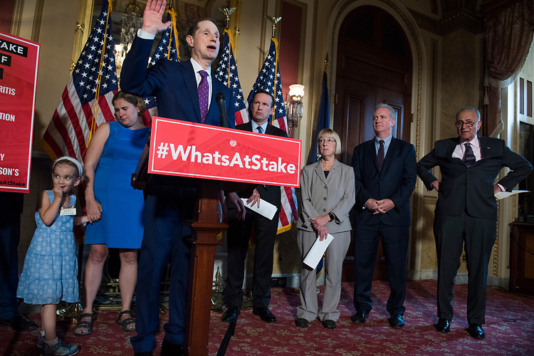 UNITED STATES - JULY 11: Sen. Ron Wyden, D-Ore., and Democratic senators conduct a news conference in the Capitol to oppose the nomination of Brett Kavanaugh to the Supreme Court because they say he would be open to questions about the constitutionality of the Affordable Care Act on July 11, 2018. Appearing are, from left, Rebecca Wood and her daughter Charlie, 6, who was born 3 1/2 months premature, Sens. Chris Murphy, D-Conn., Patty Murray, D-Wash., Chris Van Hollen, D-Md., and Charles Schumer, D-N.Y. (Photo By Tom Williams/CQ Roll Call)