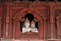 Kathmandu, Nepal.  Shiva and his Consort Parvati.  Wooden representations look down upon Durbar Square from a window in the Shiva-Parvati Temple.
