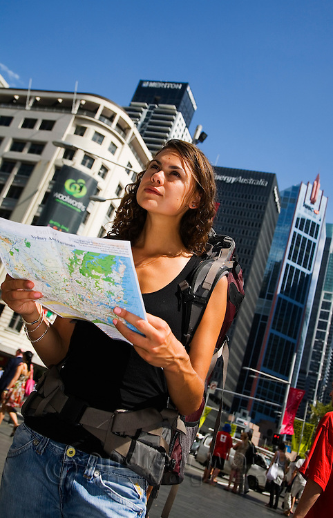 A backpacker checks her map for directions in the city.  Sydney, New South Wales, AUSTRALIA.