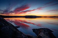 Röda skymnigsmoln över Kalvfjärden en spegelblank fjärd i Stockholms skärgård