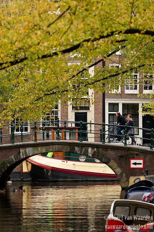 A man rides a bicycle with a woman on the back over a canal bridge in Amsterdam, the Netherlands. The fall colors decorate the canal of the Groeneburgwal, the Netherlands, North Holland.