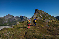 Two female hikers hiking towards Nonstind mountain peak, Moskenesøy, Lofoten Islands, Norway