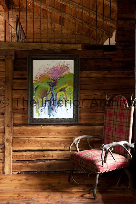 A chair made of antlers in the living room is upholstered in a tartan fabric