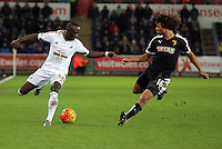 (L-R) Modou Barrow of Swansea against Nathan Ake of Watford during the Barclays Premier League match between Swansea City and Watford at the Liberty Stadium, Swansea on January 18 2016