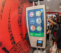 "Diners order at a ""Create Your Taste"" kiosk at a McDonald's in New York on Tuesday, August 4, 2015. The interactive iPad-like digital displays allow customers to customize their order with toppings, new sauces, etc. and have them delivered to their table in a few minutes. McDonald's, which has seen same-store sales drop over three years, is using the kiosks to compete with fast casual restaurants such as Chipotle, Fatburger and a host of others. (© Richard B. Levine)"